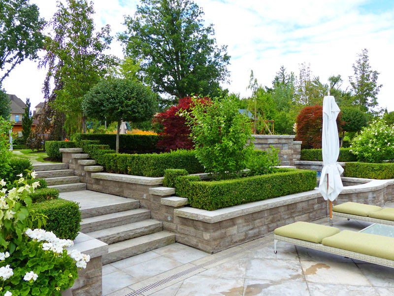 Landscape construction, exterior living area, retaining wall installation, stone pavers